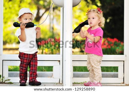 toddler girls talking by the city phones - stock photo