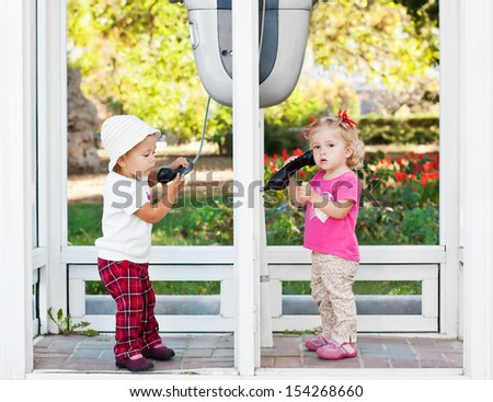 toddler girls talking by the city phones (not a traidmark) - stock photo