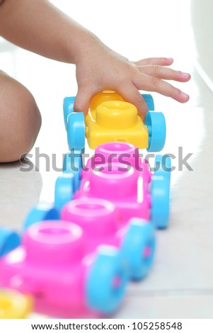 Toddler hand building a line of train coaches - stock photo