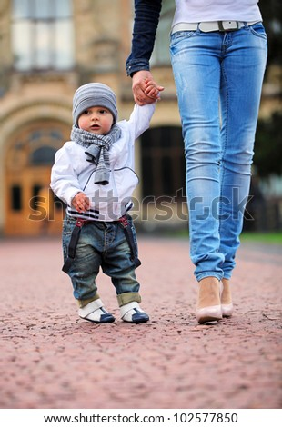 Toddler holding mother's hand outdoors - stock photo