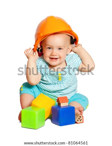 Toddler in hardhat plays  with toy blocks over white background - stock photo