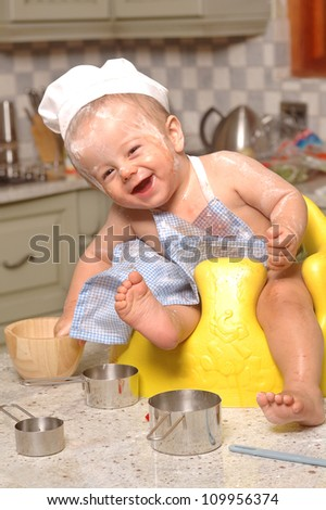 Toddler in kitchen with chef uniform on - stock photo