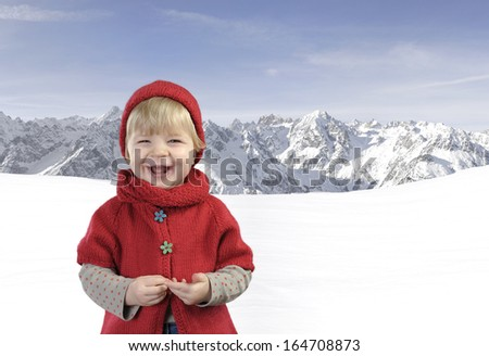 toddler in red knitted hat in the mountains
