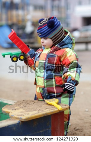 Toddler is playing with toy car at outdoor playground - stock photo