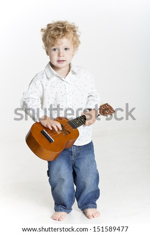 Toddler is playing with ukulele