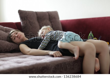 Toddler is sleeping on his mother at home