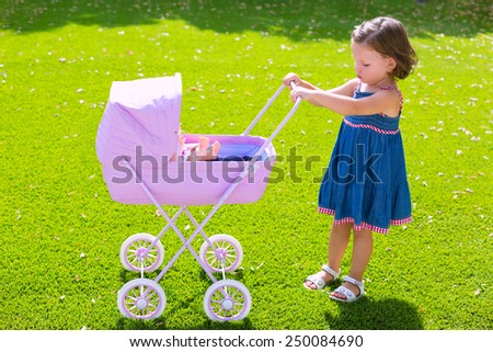 Toddler kid girl playing with baby cart in green turf grass garden - stock photo