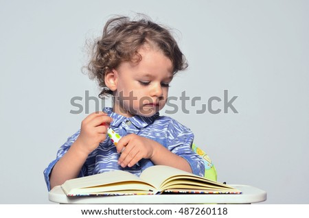 Toddler learning how to write and read. Small kid having fun preparing for school and drawing on a book.