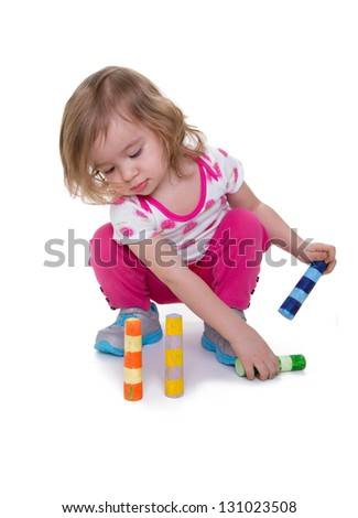 Toddler learning skills by paying attention to colorful crayons. Isolated on white with copy space.
