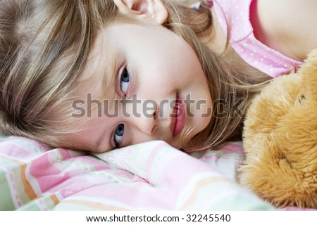 Toddler lying in bed with her teddy bear - stock photo