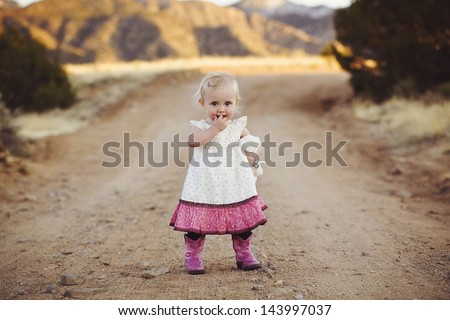 Toddler on dirt road in cowboy boots