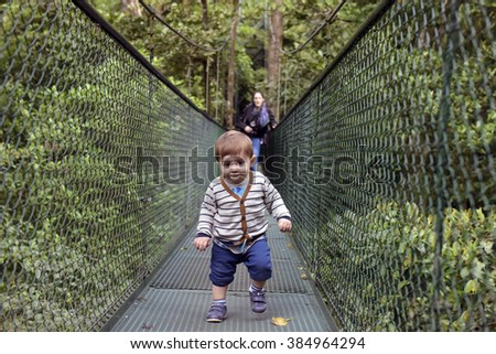 Toddler on hanging bridges in rainforest, Costa Rica - stock photo