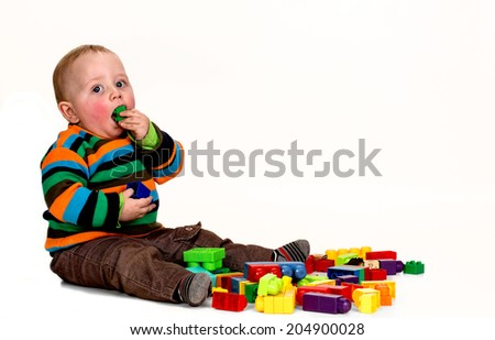 Toddler plaing with colored bricks - stock photo