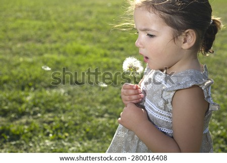 Toddler playing and blowing on a dandelion over green background. Three years old