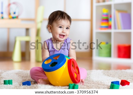 Toddler playing with a shape sorter - stock photo
