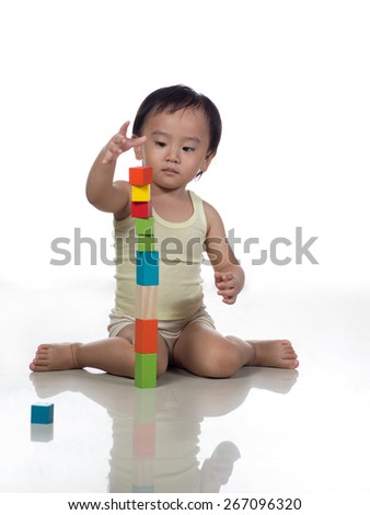 Toddler playing with colorful building blocks - stock photo