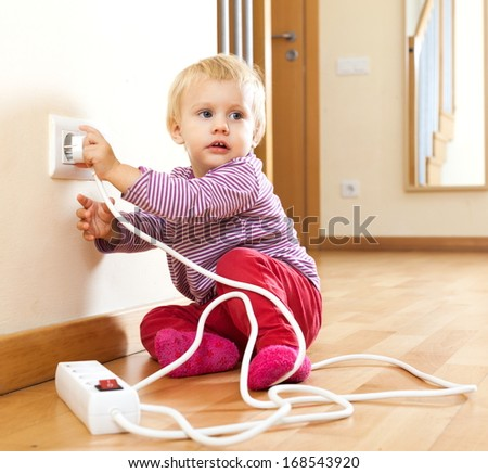 Toddler playing with  electric equipment at home - stock photo