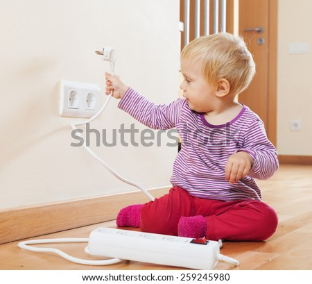 Toddler playing with electrical extension and outlet on floor at home - stock photo