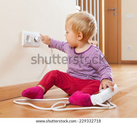 Toddler playing with extension cord and  electric outlet at home - stock photo