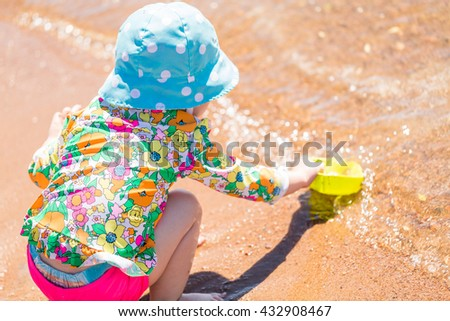 Toddler playing with sand toys on the beach.