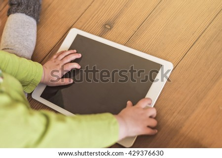 toddler playing with tablet device on a wooden floor - stock photo
