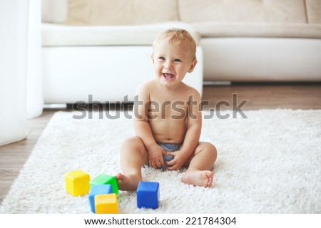 Toddler playing with toys on a white carpet at home - stock photo