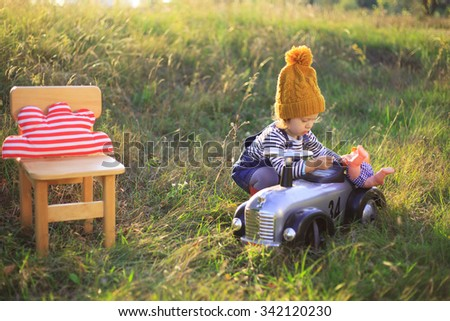 Toddler playing with vintage toy car outdoors - stock photo