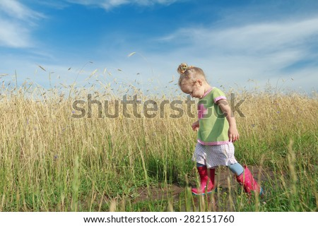 Toddler preschooler blonde girl is going down dirt road among farm field - stock photo