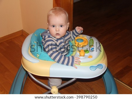 Toddler sitting in a walker - stock photo