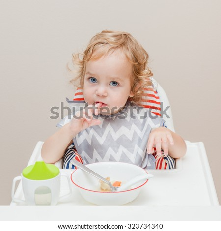 Toddler sitting on highchair with tray ready to eat in the kitchen. Child putting his finger into mouth and sucking it. Plate is full of vegetarian baby soup. - stock photo