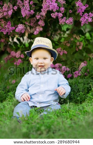 Toddler sitting on the grass in a meadow. A baby on the background of nature. Child in flowers. Kid walking on the street in the summer. Summer scene. Summertime, springtime Concept of childhood - stock photo