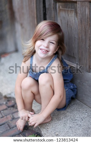 Toddler smiling in alley - stock photo