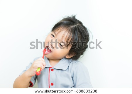 Toddler smiling while brushing her teeth.Little beautiful asian girl brushing teeth, healthy concept.