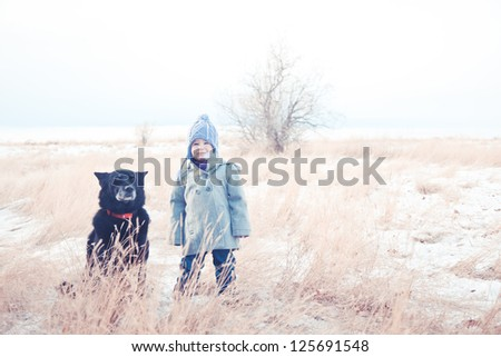 Toddler stands in the snow and tall grass with her dog. - stock photo