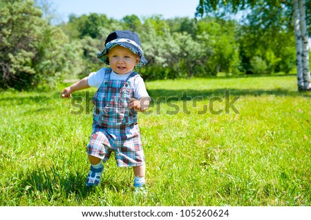 Toddler taking first steps in a park - stock photo