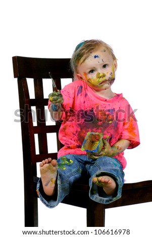 Toddler thoroughly enjoying painting herself and her clothes.