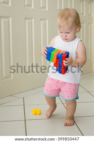 Toddler walking and playing with colourful blocks