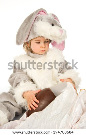 Toddler wearing bunny costume unwrapping chocolate easter egg. - stock photo