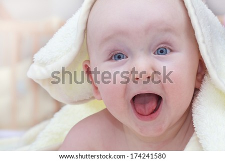 toddler with blue eyes looking out from under blanket - stock photo