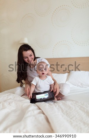 toddler with her mother playing on the bed in the tablet, children and gadgets, home comfort, care, attention - stock photo