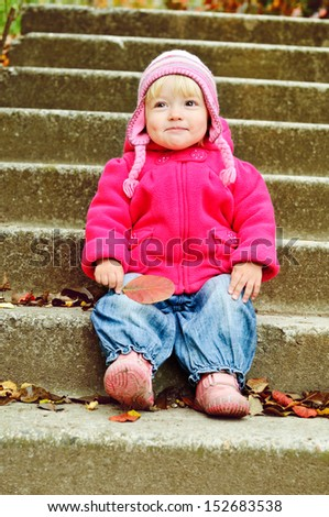 toddler with leaf in fall time - stock photo