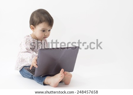 Toddler with notebook very curious - stock photo