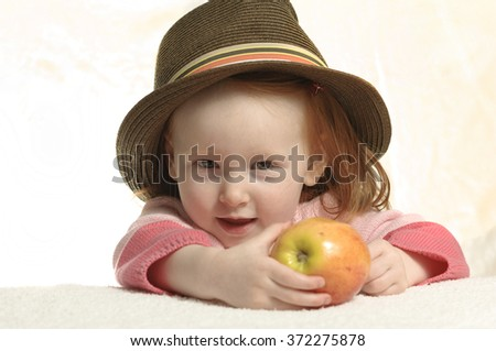 Toddler with red hair wearing a hat eating an apple