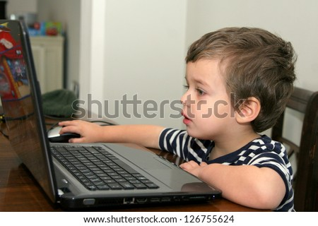 Toddler with striped shirt looking at computer - stock photo