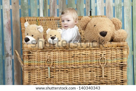 toddler with teddy bears standing in a straw trunk