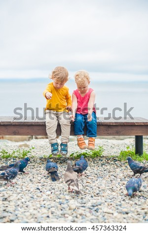 Toddlers boy and girl sitting on a bench near the sea and fed the pigeons with bread