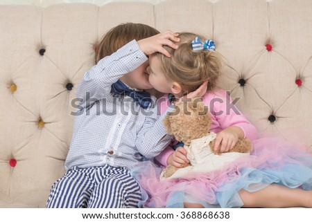 Toddlers love.  Boy and girl sitting on the couch. Valentine's Day. Love story