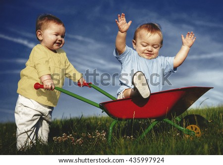Toddlers Playing Together Field Outdoors Concept - stock photo