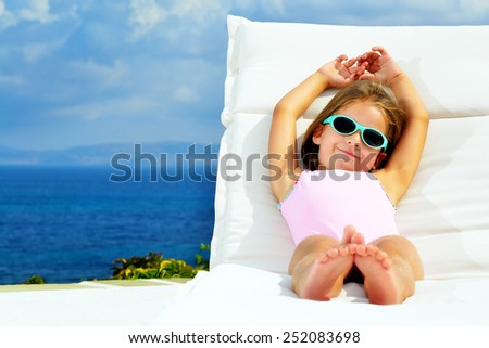 Todler girl relaxing on sunbed - stock photo