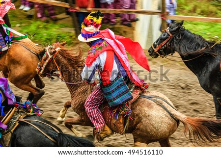 Todos Santos Cuchumatan, Guatemala - November 1, 2011: Traditionally dressed drunken jockeys race up & down dirt track on horseback in unique All Saints' Day celebration in highland town